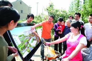 李全兴(图中穿橙色T恤男子)向村民讲解山泉新村小区规划图资料图片