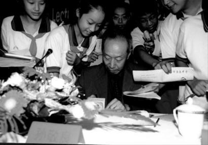 """2001年,在上海举行的""""空间周""""活动上,孙敬良为""""小航天迷""""们签名"""