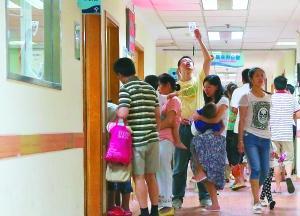 昨日,上海儿童医学中心,输液拔针处多名家长抱着孩子排队等候。高温来临,门诊量飙升,从昨天8时到17时,该院门诊接待5200例。早报记者 王辰 图