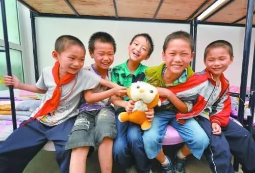 7月2日,留坝县城关小学的几名学生在宿舍玩耍。学生住宿用的床上用品都由当地政府提供。