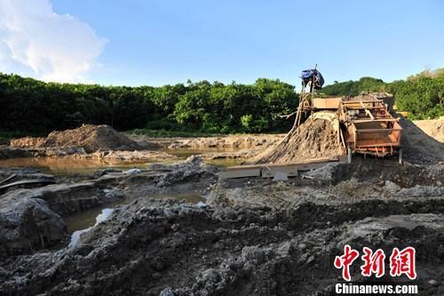 """7月5日,承包商王某所承包""""改良土地""""现场被挖出多个水坑并有淘金工具。中新社发 骆云飞 摄"""