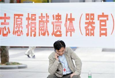 2013年5月7日,南京,一名红十字会工作人员在志愿捐献遗体(器官)的横幅前打电话。图/CFP